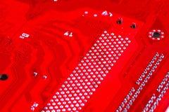 Primer del circuito electrónico rojo de la placa madre con el procesador Imagen de archivo