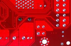 Primer del circuito electrónico rojo de la placa madre con el procesador Fotos de archivo