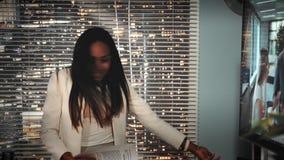 Primer del cliente femenino afroamericano que rasga para arriba el contrato del negocio con el colorist en estudio de la producci almacen de video