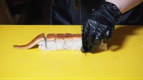 Primer del cocinero de sushi que prepara los rollos europeos con la anguila en una tabla de cocina amarilla grande Cap?tulo tradi metrajes