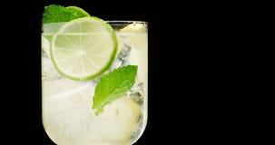 Primer del coctail Mojito, agua del tonik con la menta y limón y cal y cubos de hielo metrajes