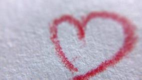 Primer del corazón rojo que dibuja por el lápiz el día de tarjeta del día de San Valentín