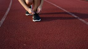 Primer del corredor femenino que ata cordones en las zapatillas de deporte metrajes