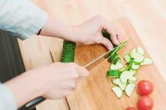 Primer del corte femenino de las manos en los pepinos frescos del corte en una tabla de cortar de madera al lado de los tomates r Fotos de archivo