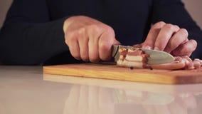 Primer del corte que taja un pedazo de tocino en pedazos más pequeños Primer de las manos masculinas que cortan un pedazo de toci almacen de video