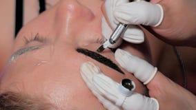Primer del cosmetologist que hace procedimiento microblading Maquillaje permanente Tatuaje permanente de cejas metrajes