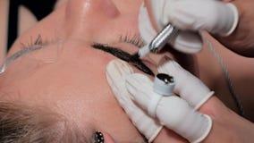 Primer del cosmetologist que hace procedimiento microblading Maquillaje permanente Tatuaje permanente de cejas almacen de video