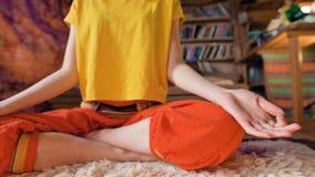 Primer del cuerpo de una chica joven en la posición de loto que se sienta en un cuarto del arte en una piel blanca de la piel rod almacen de video