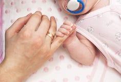 Primer del dedo de la madre de la explotación agrícola de la mano del bebé Imagen de archivo