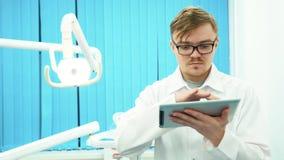 Primer del dentista del hombre joven en la capa blanca que mira su tableta en oficina dental Cuidado dental almacen de video