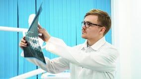 Primer del dentista del hombre joven en la capa blanca y los vidrios que miran el rayo de X en oficina dental Cuidado dental almacen de metraje de vídeo