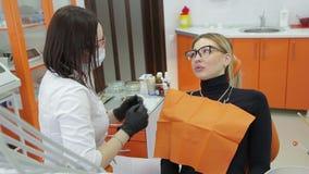 Primer del dentista que examina los dientes del ` s de la mujer joven metrajes