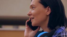 Primer del discurso femenino moreno bronceado en el teléfono almacen de metraje de vídeo