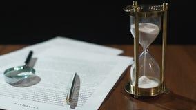 Primer del documento y reloj de arena en la tabla, expiración del período de la validez del contrato metrajes