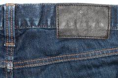 Primer del dril de algodón: fondo de la textura de la etiqueta de cuero en la mezclilla azul Fotos de archivo