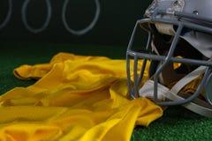 Primer del engranaje y del jersey de la cabeza del fútbol americano que mienten en césped artificial Foto de archivo libre de regalías