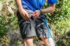 Primer del escalador del muslo con el equipo en la correa, soportes cerca de la roca fotografía de archivo libre de regalías