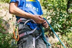 Primer del escalador del muslo con el equipo en la correa, soportes cerca de la roca imagenes de archivo
