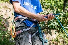 Primer del escalador del muslo con el equipo en la correa, soportes cerca de la roca foto de archivo libre de regalías