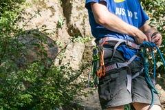Primer del escalador del muslo con el equipo en la correa, soportes cerca de la roca imagen de archivo libre de regalías
