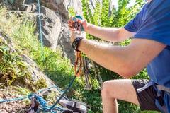 Primer del escalador del muslo con el equipo en la correa, soportes cerca de la roca foto de archivo