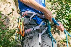 Primer del escalador del muslo con el equipo en la correa, soportes cerca de la roca fotos de archivo