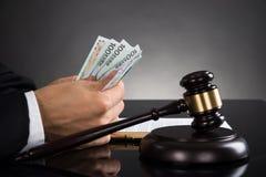 Primer del escritorio de Counting Banknote At del juez imagen de archivo