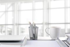 Primer del escritorio delante de la ventana grande Fotografía de archivo libre de regalías