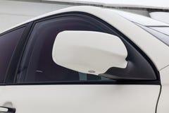 Primer del espejo izquierdo lateral con el repetidor de la señal de vuelta y la ventana de la carrocería SUV blanco en la calle q imagen de archivo libre de regalías