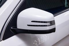 Primer del espejo izquierdo lateral con el repetidor de la se?al de vuelta y la ventana de la carrocer?a SUV blanco en la calle q foto de archivo