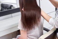 Primer del estilista que peina el pelo del ` s del cliente en salón imagenes de archivo