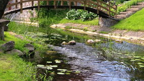 Primer del flujo de corriente del agua de río entre las piedras debajo del puente metrajes