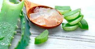 Primer del gel de Vera del áloe en el fondo de madera blanco Hoja y gel cortados orgánicos, ingredientes cosméticos orgánicos nat fotos de archivo libres de regalías