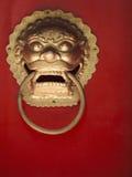 Primer del golpeador de puerta adornado del oro en puerta roja Fotografía de archivo