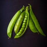 Primer del guisante verde y de las vainas de guisante en un fondo oscuro Foto de archivo