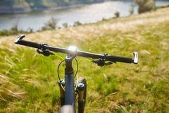 Primer del handlaber de la bicicleta de la montaña contra paisaje hermoso en la estación de verano Fotografía de archivo