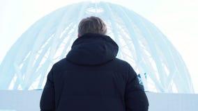 Primer del hombre blanco en la chaqueta negra que mira la construcción blanca grande Visión desde la parte posterior almacen de video