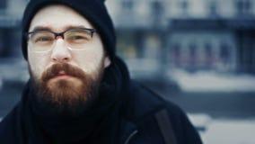Primer del hombre caucásico en el casquillo y los vidrios del sombrero que dan vuelta principales en la calle del invierno almacen de metraje de vídeo