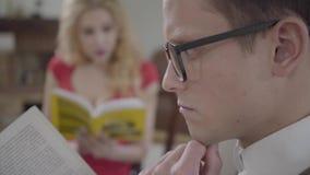 Primer del hombre concentrado joven en vidrios que lee el libro en el primero plano mientras que mujer rubia bonita que habla con almacen de video