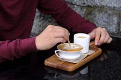 Primer del hombre de la mano de Asia en la camisa roja que revuelve el azúcar en pequeña taza blanca de café caliente foto de archivo libre de regalías