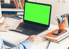 Primer del hombre de la mano usando un ratón y de mecanografiar en el ordenador portátil verde de la pantalla en la tabla blanca, imagen de archivo