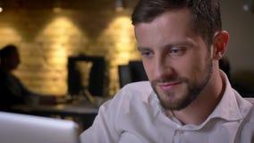 Primer del hombre de negocios caucásico alegre joven que mecanografía en el ordenador portátil que mira la cámara y la sonrisa almacen de metraje de vídeo
