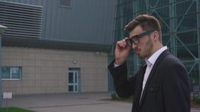 Primer del hombre de negocios elegante hermoso confiado que pone en los vidrios mientras que espera su vuelo almacen de video