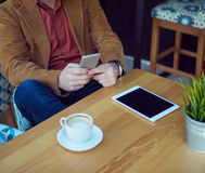 Primer del hombre de negocios en cafetería usando su teléfono Foto de archivo libre de regalías