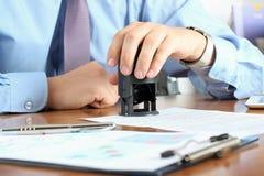 Primer del hombre de negocios Hand Pressing un sello en el documento en th Fotos de archivo