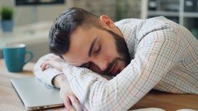 Primer del hombre de negocios joven hermoso que duerme en la oficina que miente en el ordenador portátil almacen de metraje de vídeo