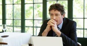 Primer del hombre de negocios pensativo que se sienta delante del ordenador portátil almacen de video