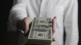 Primer del hombre de negocios que da un barril de billetes de dólar El concepto de salarios caridad almacen de metraje de vídeo