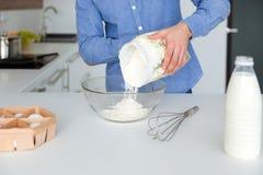Primer del hombre en la camisa azul que prepara la pasta en cocina Fotografía de archivo libre de regalías