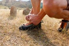 Primer del hombre irreconocible que pone sus zapatos que suben anaranjados y que ata cordones al aire libre antes de subida de la Imágenes de archivo libres de regalías